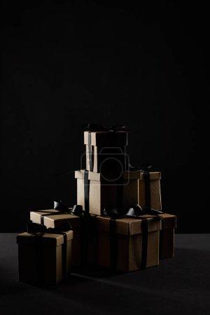 Photo pour Coffrets cadeaux en carton avec rubans noirs dans l'obscurité isolé sur noir, concept Black Friday - image libre de droit