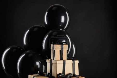 Photo for Bunch of black balloons near stack of gift boxes isolated on black, black Friday concept - Royalty Free Image
