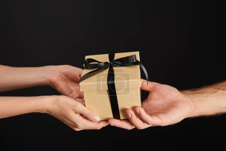 Photo for Cropped view of man and woman holding cardboard gift box with ribbon isolated on black, black Friday concept - Royalty Free Image