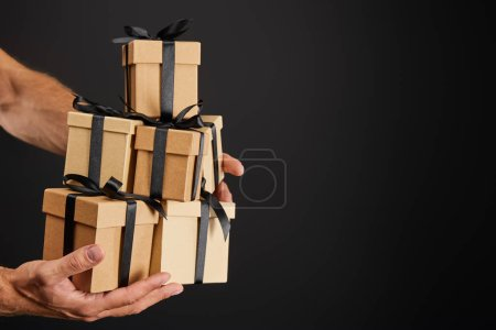 abgeschnittene Ansicht eines Mannes mit Geschenkkartons aus Pappe mit Schleifen, isoliert auf schwarzem, schwarzem Freitag-Konzept