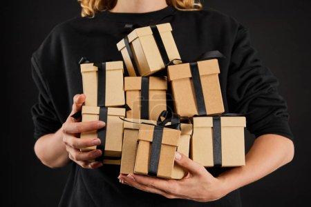 Photo pour Vue en coupe d'une femme tenant des boîtes-cadeaux en carton avec des rubans isolés sur noir et noir Concept du vendredi - image libre de droit