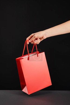 vue partielle de la femme tenant des sacs à provisions rouges isolés sur noir, concept vendredi noir