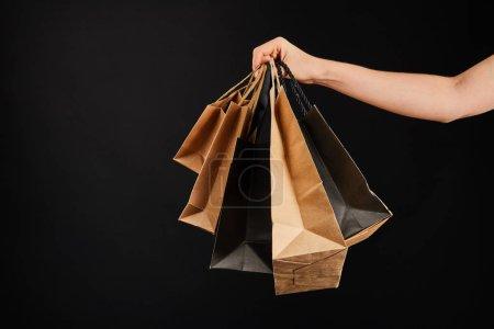Photo pour Vue partielle d'une femme tenant des sacs de papier isolés sur noir, noir Concept du vendredi - image libre de droit