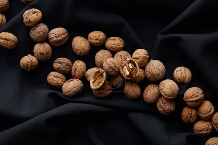 Photo for Top view of brown nuts on black cloth - Royalty Free Image