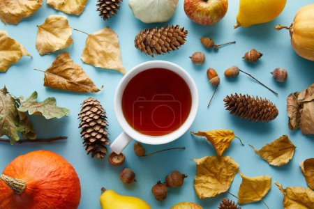 top view of mug with tea near autumnal decoration on blue background