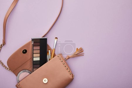 top view of eye shadow and blush near cosmetic brushes in bag isolated on violet