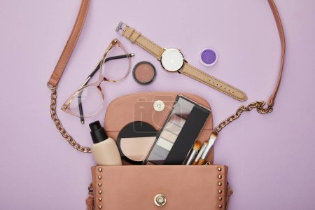 Photo for Top view of watch near glasses and bag with girls stuff isolated on violet - Royalty Free Image