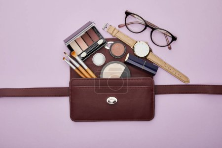 Photo pour Top view of decorative cosmetics near watch and glasses isolated on violet - image libre de droit