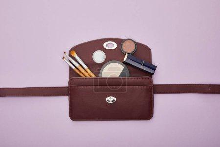 Photo pour Vue du dessus des cosmétiques décoratifs près du sac isolé sur violet - image libre de droit
