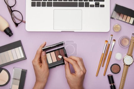 Photo pour Cropped view of woman holding eye shadow near laptop and decorative cosmetics isolated on violet - image libre de droit
