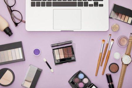 Photo pour Vue de dessus de l'ordinateur portable près de cosmétiques décoratifs isolés sur violet - image libre de droit
