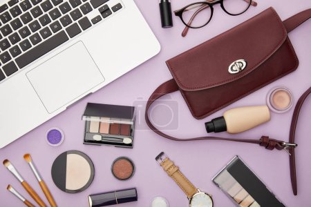 Photo for Top view of bag and decorative cosmetics near laptop isolated on violet - Royalty Free Image