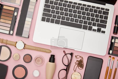 top view of laptop near decorative cosmetics and glasses isolated on pink