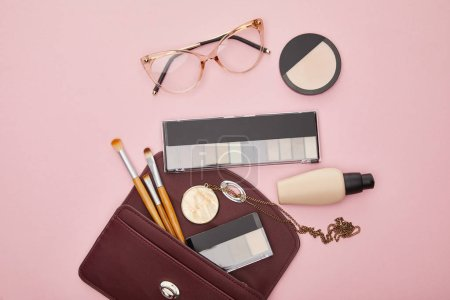 Photo for Top view of glasses near bag with decorative cosmetics isolated on pink - Royalty Free Image