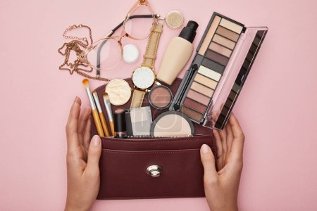 Photo pour Top view of woman near bag with decorative cosmetics isolated on pink - image libre de droit