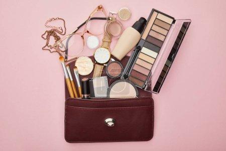 Photo pour Vue du haut du sac brun près des cosmétiques décoratifs et montre isolée sur rose - image libre de droit