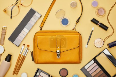 Photo pour Top view of bag near decorative cosmetics and necklace isolated on yellow - image libre de droit