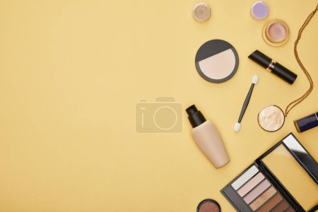 Photo pour Top view of face foundation and eye shadow isolated on yellow - image libre de droit
