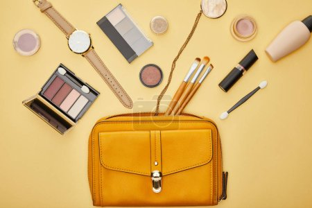 Photo pour Top view of bag near eye shadow and watch isolated on yellow - image libre de droit