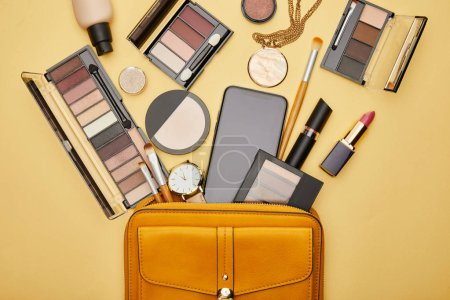 top view of bag with decorative cosmetics and smartphone with blank screen isolated on yellow