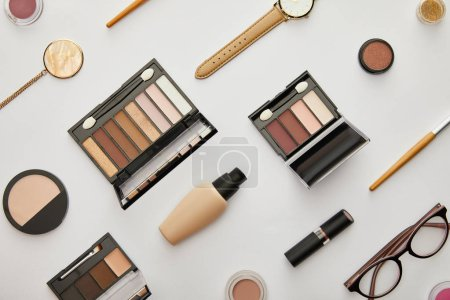 Photo pour Top view of face foundation near eye shadow and accessories isolated on grey - image libre de droit