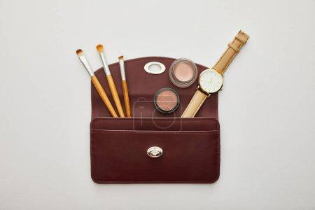 Photo pour Vue de dessus des cosmétiques décoratifs près de montre en sac isolé sur gris - image libre de droit