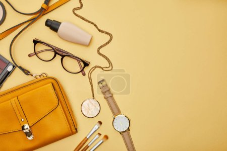 Photo pour Top view of bag near glasses, necklace and watch isolated on yellow - image libre de droit