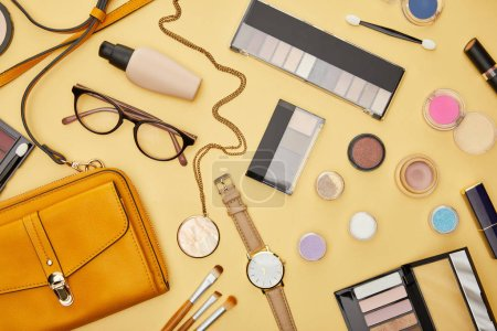 Photo pour Top view of bag near glasses and decorative cosmetics isolated on yellow - image libre de droit