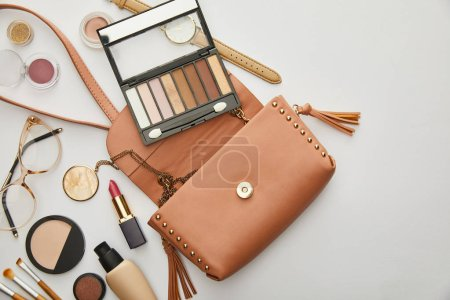 Photo for Top view of bag near decorative cosmetics and glasses isolated on grey - Royalty Free Image