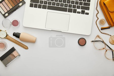 Photo for Top view of laptop near yellow bag and decorative cosmetics isolated on grey - Royalty Free Image