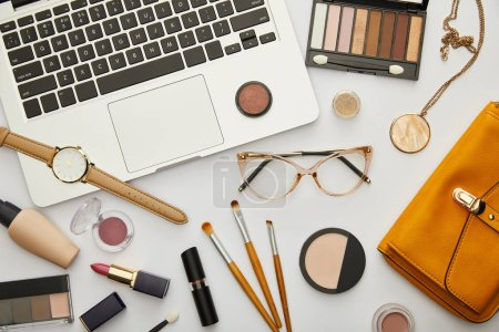 top view of laptop near yellow bag, glasses and decorative cosmetics isolated on grey