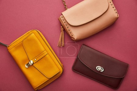 Photo pour Top view of leather and stylish bags isolated on crimson - image libre de droit