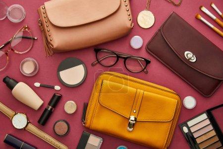 Photo pour Top view of stylish bags near decorative cosmetics isolated on crimson - image libre de droit