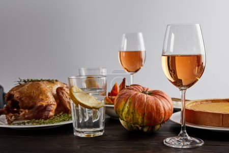 Photo for Baked pumpkin, grilled turkey, pumpkin pie, glasses with rose wine and lemon water on wooden table isolated on grey - Royalty Free Image