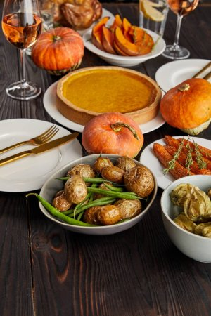 Photo for Pumpkin pie, baked potatoes, pumpkins and carrots on wooden table - Royalty Free Image