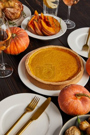 Photo for Pumpkin pie and baked pumpkins served on wooden table - Royalty Free Image