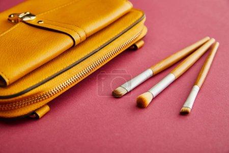 Photo pour Gros plan des pinceaux cosmétiques près du sac jaune sur cramoisi - image libre de droit