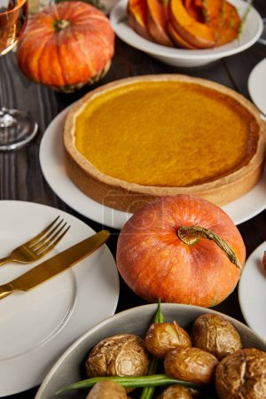 Photo for Pumpkin pie, baked potatoes and pumpkins served on white plates on wooden table - Royalty Free Image