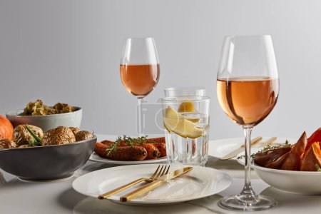 glasses with rose wine and lemon water, baked potatoes and carrots, white plates and cutlery on marble table isolated on grey