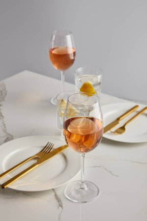 glasses with rose wine and lemon water near white plates with forks and knives on marble table isolated on grey