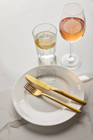 Photo for White plate with golden knife and fork near glasses with lemon water and rose wine on marble table - Royalty Free Image