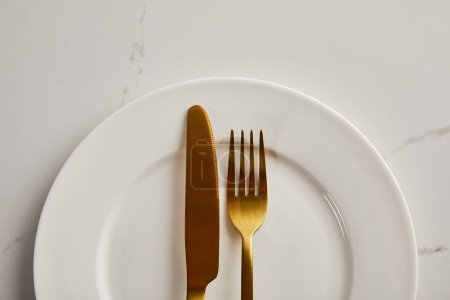 Photo for Top view of golden knife and fork on clean white plate on marble table - Royalty Free Image