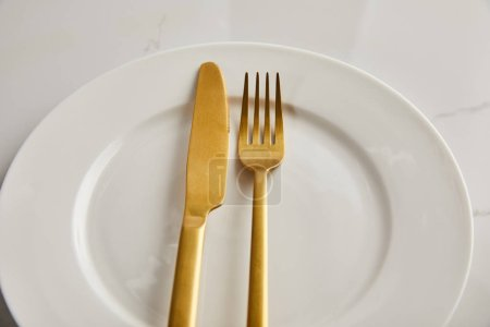 Photo for Golden knife and fork on clean white plate on marble table - Royalty Free Image
