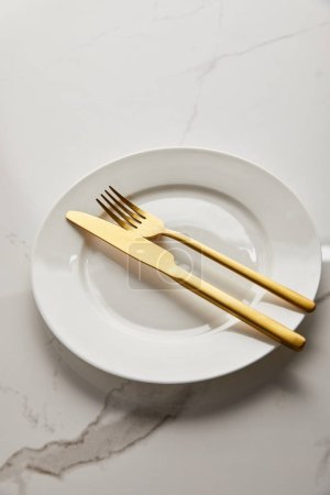 Photo for Clean white plate with shiny golden knife and fork on marble table - Royalty Free Image
