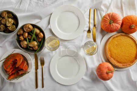 Photo for Top view of served dinner with pumpkin pie, baked vegetables and fresh whole pumpkins on white tablecloth - Royalty Free Image