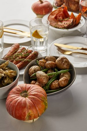 Photo for Festive thanksgiving dinner with grilled vegetables and whole pumpkins served on white marble table - Royalty Free Image