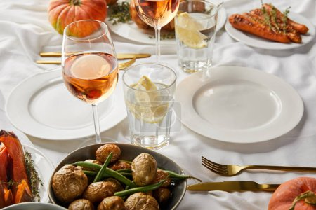Photo for Festive thanksgiving dinner with baked vegetables and glasses with rose wine and lemon water on white tablecloth - Royalty Free Image