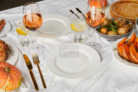Photo for Festive dinner with baked seasonal vegetables near glasses with rose wine and lemon water served on white tablecloth - Royalty Free Image