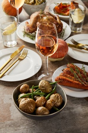 Photo for Baked potato with asparagus near grilled carrot and turkey, and glasses with rose wine and lemon water on stone table - Royalty Free Image