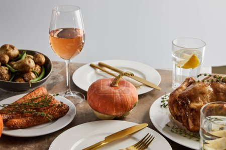 Photo for Thanksgiving day dinner with baked vegetables, grilled turkey and glasses with rose wine and lemon water isolated on grey - Royalty Free Image